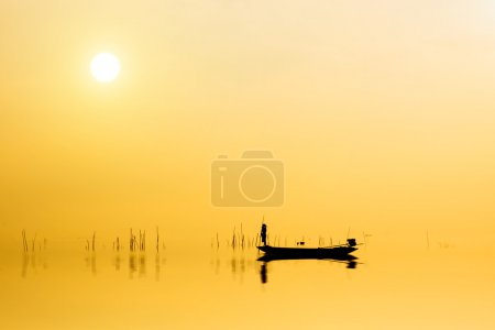 Photo for Beautiful sky and Silhouettes of Minimal fisherman at the lake, Thailand. - Royalty Free Image