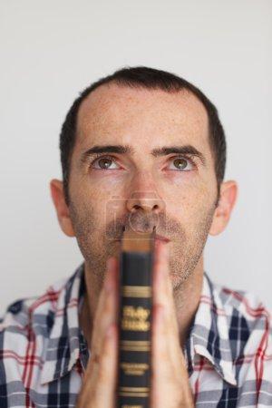 Photo pour Gros plan de jeune homme priant. Mans mains jointes en prière avec Sainte Bible - image libre de droit