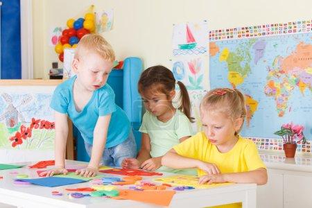 Photo pour Trois enfants d'âge préscolaire en classe - image libre de droit