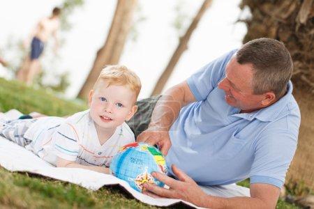 Photo pour Portrait de petit-fils et grand-père souriant avec globe terrestre - image libre de droit