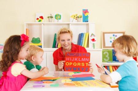 Photo pour Enfants d'âge préscolaire en classe avec l'enseignant - image libre de droit