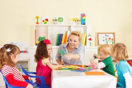 Photo pour Enfants d'âge préscolaire en classe avec le professeur - image libre de droit