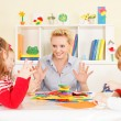 Preschool: Young smiling teacher discussing with g...