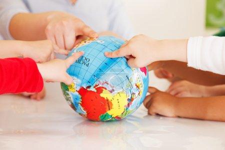 Photo pour Des enfants multiculturels mains sur un globe - image libre de droit