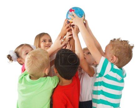 Photo pour Des enfants souriants du monde entier tenant un globe - image libre de droit