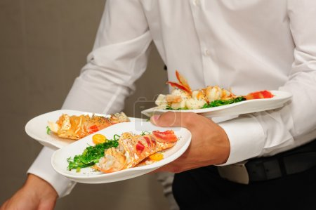 Waiter holds plates with lobsters