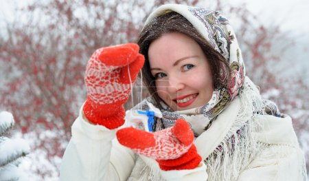 Photo pour Beautiful young Russian folk woman in winter park with christmas tree toy - image libre de droit