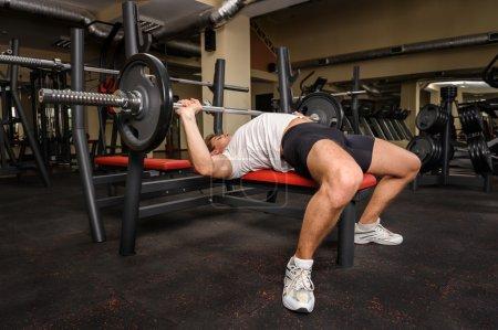jeune homme couché entraînement réside dans la salle de gym