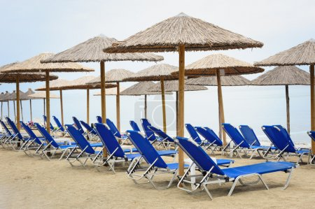 Reed umbrellas and deck chairs at the beach