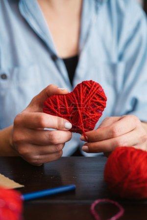 Photo pour Femme créant coeur de laine rouge - image libre de droit