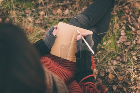 Woman in nature writing in a notebook