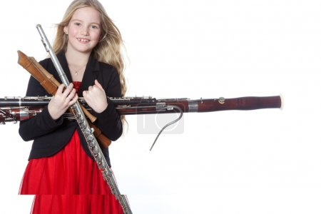 young girl holds woodwind instruments in studio