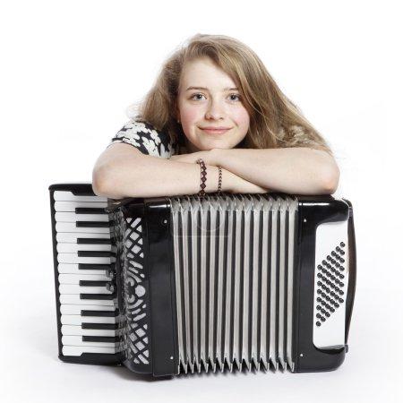 Smiling teenage girl on the floor of studio with accordion