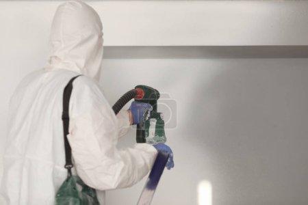 Photo pour Maître peintre en costume blanc peint mur avec un pistolet pulvérisateur. Peinture murale maître services concept - image libre de droit