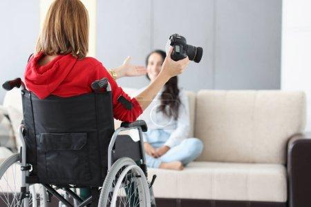 Photo pour Femme en fauteuil roulant avec caméra effectue une séance photo à la maison. Concept de professions pour les personnes handicapées - image libre de droit