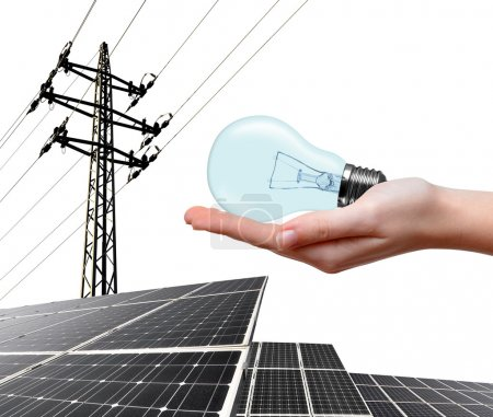 Hand holding lightbulb. In the background solar panel and high voltage tower.