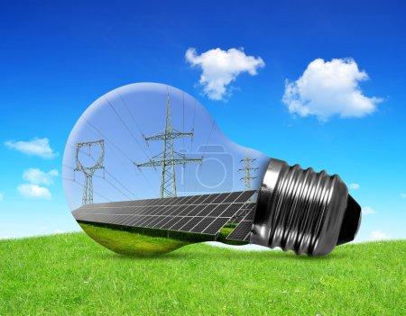 Foto de Paneles solares con torres de alta tensión en la bombilla. Concepto de energía verde. - Imagen libre de derechos