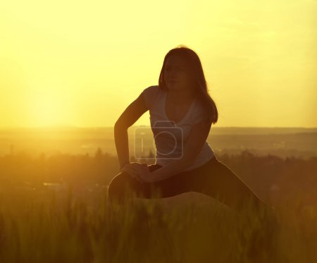 Silhouette of young woman stretching on a meadow