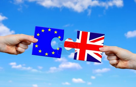 Hands holding puzzle with flag of the UK and EU.