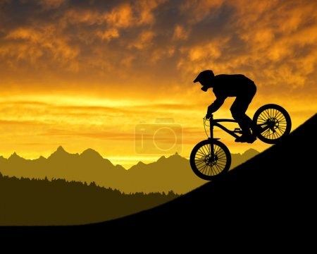 Silhouette of the cyclist on downhill bike at suns...