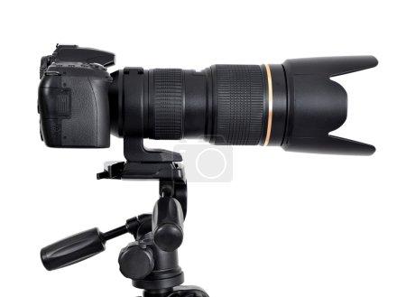 Foto de DSLR camera with zoom lense on a tripod isolated on white background - Imagen libre de derechos