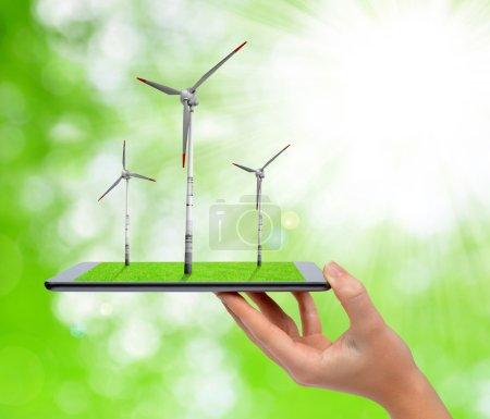 Foto de Tableta digital de mano con turbinas eólicas. Concepto de energía verde . - Imagen libre de derechos