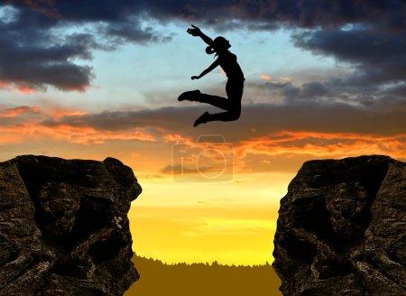 Photo pour Silhouette de la jeune fille sautant par-dessus le fossé au coucher du soleil - image libre de droit