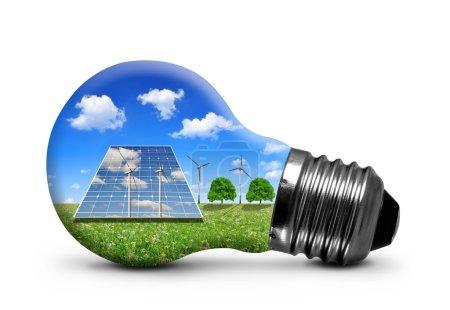 Foto de Paneles solares y turbinas eólicas en bombilla aislada  . - Imagen libre de derechos