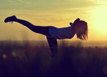 Photo pour Silhouette de jeune femme s'étirant sur une prairie au coucher du soleil - image libre de droit