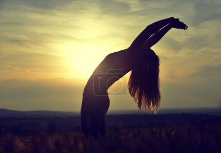 Silhouette of young woman stretching