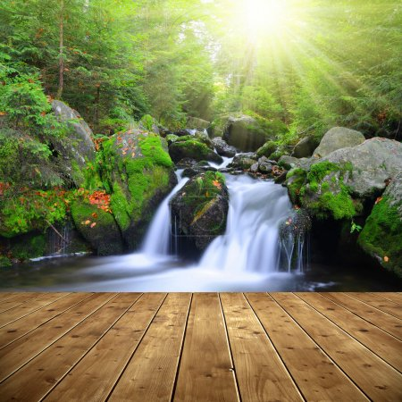 Photo for Waterfall on a mountain creek. In the foreground a wooden planks. - Royalty Free Image