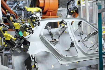 Photo pour En tôle estampée partie de la nouvelle voiture dans l'usine de voiture. Le robot est partie pour voiture neuve. - image libre de droit