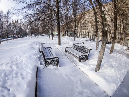 Pushkino, Russia, on January 26, 2015. Winter city landscape of by fisheye view. Boulevard and bench under snow