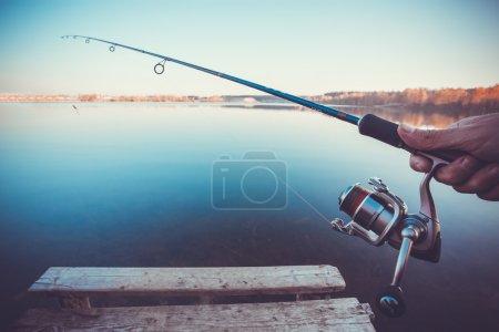 Photo pour Main avec filature et reel sur le lac de l'été - image libre de droit