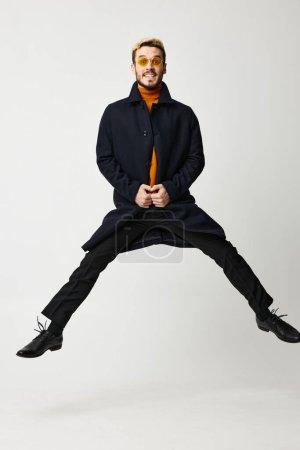 Photo pour Homme à la mode en manteau noir sauté avec les jambes écartées et pull orange Espace de copie. Photo de haute qualité - image libre de droit