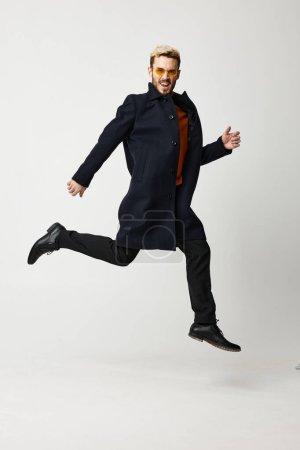 Photo pour Bel homme blond sauté en manteau noir et bottes pantalon mode tendance de la saison. Photo de haute qualité - image libre de droit
