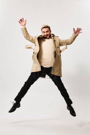 Photo pour Un homme à succès en manteau beige sauta et gesticula les mains sur un fond clair. Photo de haute qualité - image libre de droit