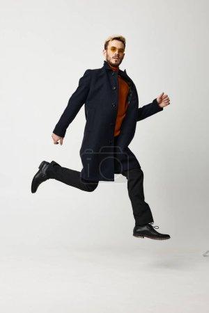 Photo pour Un homme blond en manteau a sauté et court sur le côté sur un fond clair. Photo de haute qualité - image libre de droit
