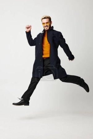 Photo pour Un homme en vêtements élégants, pantalon et bottes a sauté sur un fond clair. Photo de haute qualité - image libre de droit