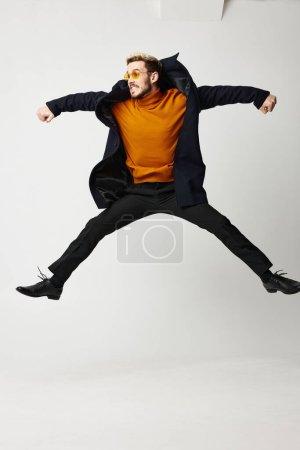 Photo pour Homme a sauté avec les jambes et les bras écartés large modèle de pull orange. Photo de haute qualité - image libre de droit