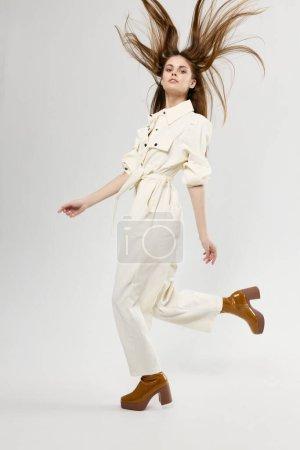 Photo pour Femme heureuse a sauté en salopette blanche et des chaussures brunes. Photo de haute qualité - image libre de droit