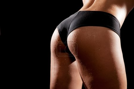 Photo for Young tanned woman with beautiful sporty buttocks wearing black sexy sporty style shorts. Water drops on wet skin - Royalty Free Image
