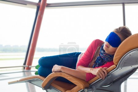 woman relaxing in eye sleep mask at airport terminal awaiting the flight