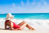 back view of long haired young woman in swimsuit and straw hat on tropical caribbean beach