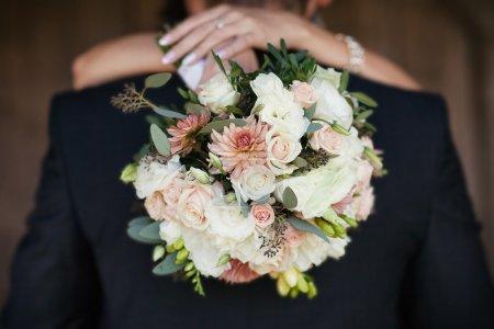 Photo pour Mariée avec un bouquet dans les mains du marié câlin - image libre de droit