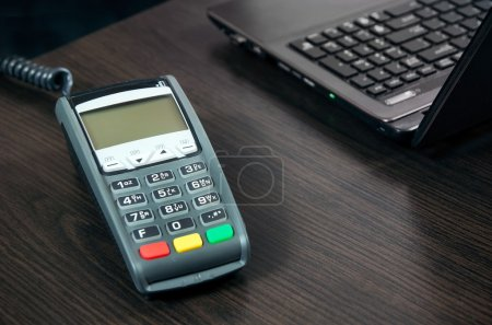 Payment terminal in the office. Laptop in the background