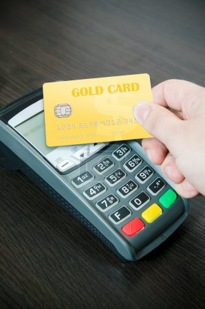 Photo for Man pays a gold card in payment terminal - Royalty Free Image