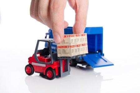 Hand nimmt Kisten aus Gabelstapler-Spielzeug. Konzept der internationalen Zusammenarbeit