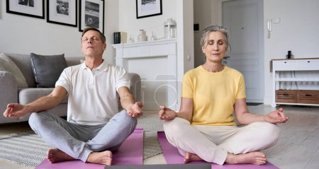 Photo for Healthy mindful old mature senior 60s couple meditating together at home. Calm serene older middle aged family do yoga breathing exercise with eyes closed feeling stress relief, life balance concept. - Royalty Free Image