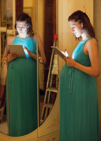 pregnant woman using tablet at home